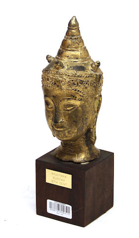 A Thai gilt painted and cast bronze head of the Buddha on wood stand 19th century