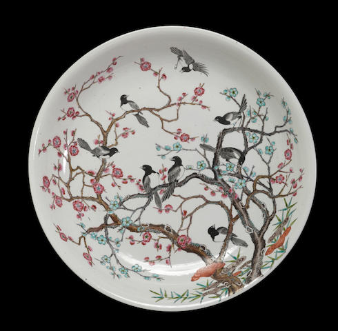 A polychrome enameled porcelain charger with magpie and prunus decoration