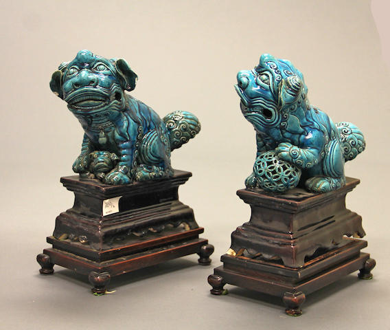 A pair of Chinese export turquoise blue glazed fu dogs 18th/19th century each attached to a wood stand