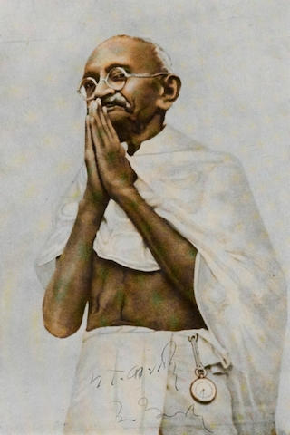 "GANDHI, MOHANDAS K.  1869-1948. Photograph Signed (""M.K. Gandhi""), 145 x 195 mm halftone reproduction of Gandhi with his hands folded in prayer, signed at the lower margin,"