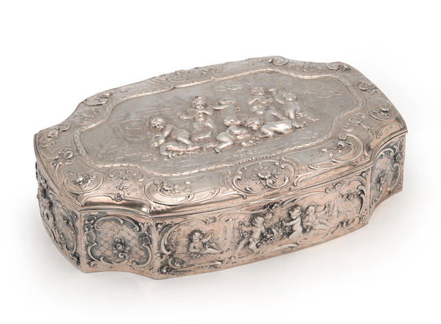 A German 800 standard silver large cartouche form table box with panel decoration of putti at various pursuits by Storck & Sinsheimer, Hanau, first quarter 20th century