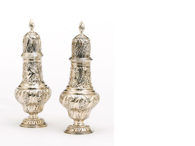 An Edward VII silver pair of large sugar casters with chased decoration by Nathan & Hayes, Chester, 1905/1906