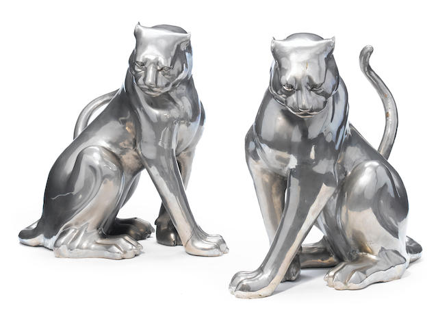 A pair of silvered metal models of panthers