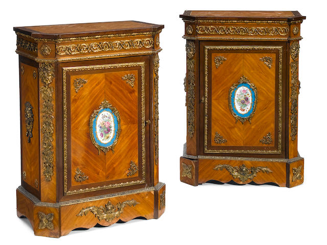 A pair of Napoleon III gilt bronze and porcelain mounted walnut side cupboards