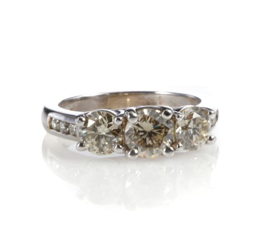 A colored diamond, diamond and white gold three stone ring