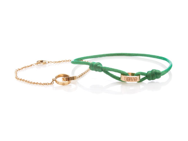 "A gold ""Love"" charm and green chord bracelet together with a double interlocking ""Love"" charm bracelet,"