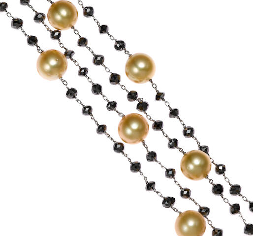 A golden cultured pearl, black briolette diamond and white gold chain length 64in