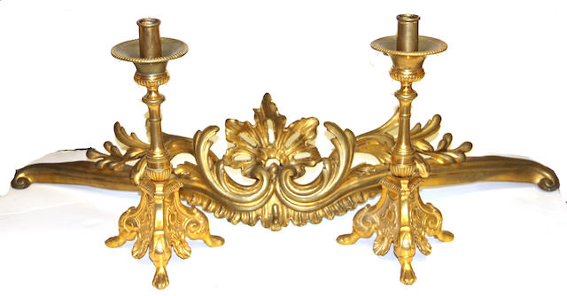 A pair of Baroque style gilt bronze candlesticks and a Rococo style gilt bronze furniture mount late 19th century