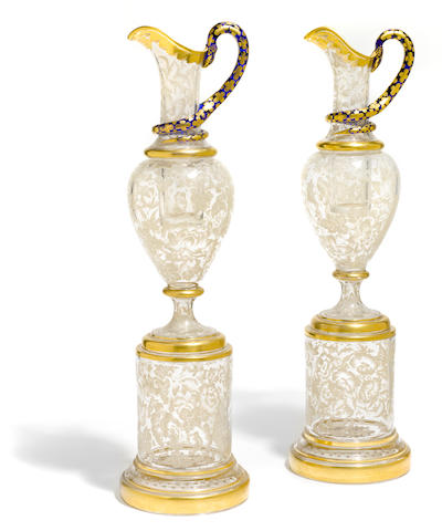 A pair of Continental paint decorated and gilt heightened clear and blue glass ewers on stands <BR />early 20th century
