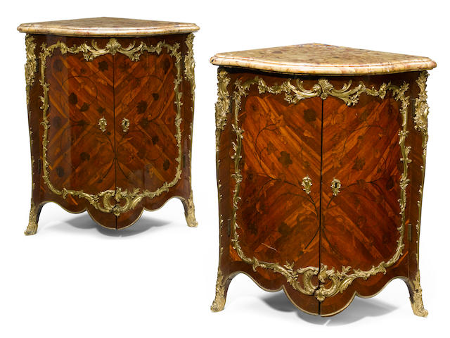 A pair of good quality Louis XV gilt bronze mounted marquetry inlaid walnut encoignures <BR />Hubert Hansen<BR />second half 18th century