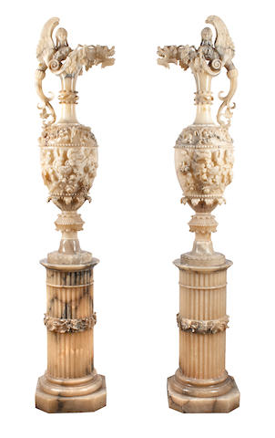 A monumental pair of Italian Renaissance Revival carved alabaster ewers on pedestals