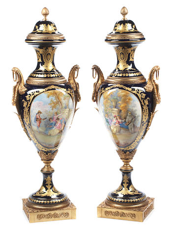 An imposing pair of gilt bronze mounted Sèvres style porcelain covered urns