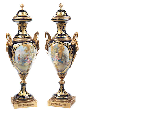 An imposing pair of gilt bronze mounted Sevres style porcelain covered urns