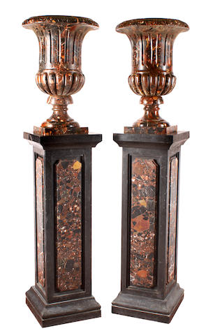 A pair of Neoclassical style carved marble urns on pedestals