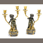 A pair of Louis XVI style gilt and patinated bronze figural two light candelabra <BR />after models by Clodion<BR />late 19th century