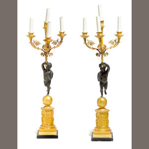 A pair of Empire style gilt and patinated bronze four light figural candelabra . 19th century with alterations