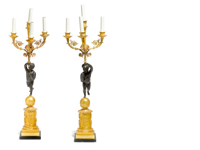 A pair of Empire style gilt and patinated bronze four light figural candelabra <BR />19th century with alterations