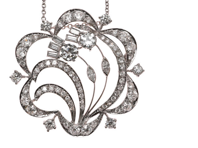 A diamond pendant/brooch with fourteen karat white gold chain