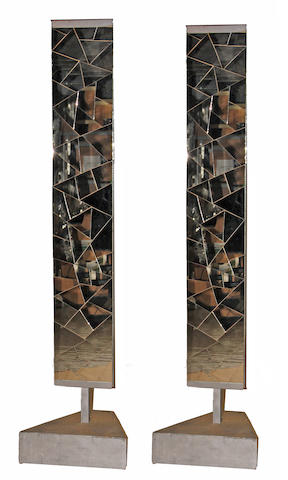 A pair of contemporary mirrored panels on silvered wood pedestals
