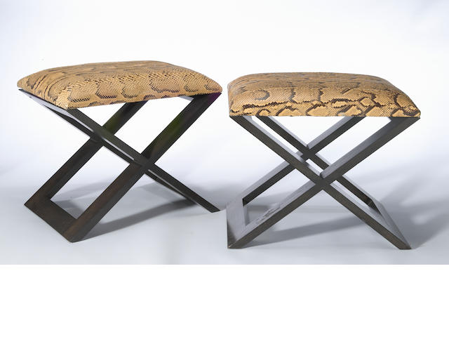 A pair of ebonized wood stools covered with reptile upholstery