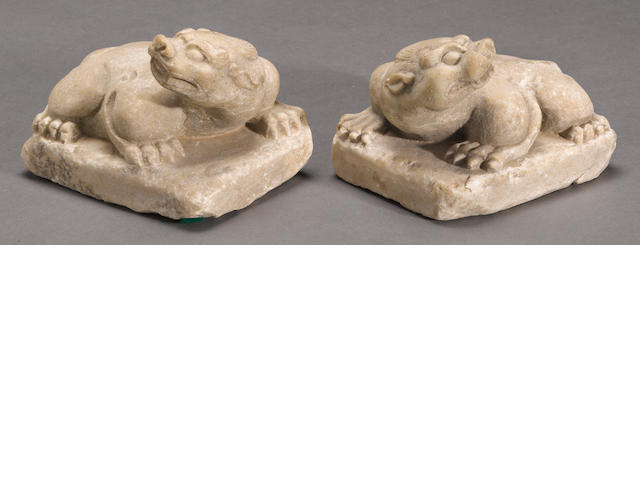 A pair of carved stone recumbent mythical beasts