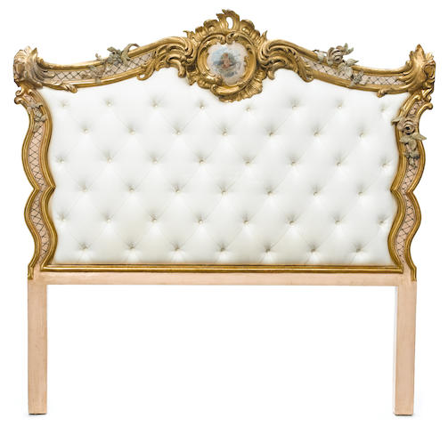 A Louis XV style parcel paint decorated and carved giltwood headboard  <BR />19th century and later