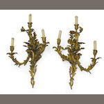 An imposing pair of Louis XV style gilt bronze three light bras de lumière <BR />late 19th century