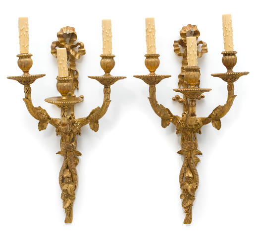 A pair of Neoclassical style carved giltwood three light bras de lumière