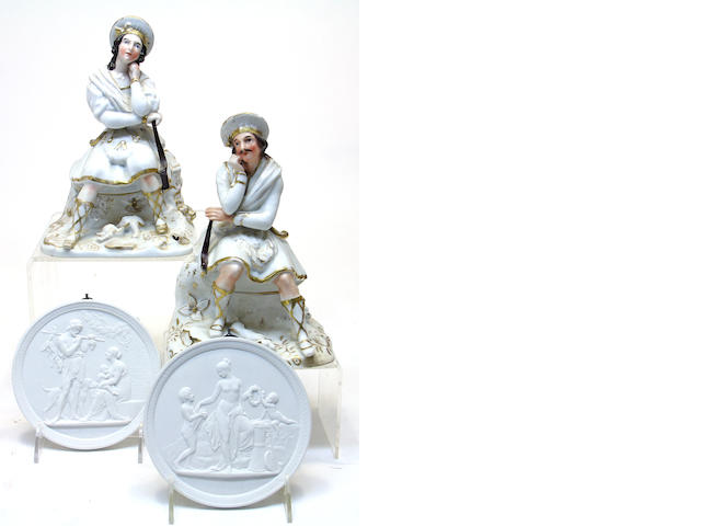 A pair of French porcelain figural cologne bottles and a pair of Royal Copenhagen bisque porcelain relief molded plaques  third quarter 19th century