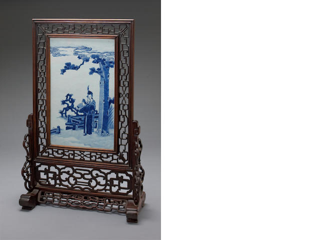 A blue and white porcelain rectangular plauqe mounted in a mixed wood table screen