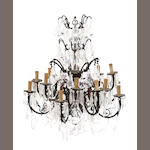 A Louis XV style patinated bronze and glass sixteen light chandelier