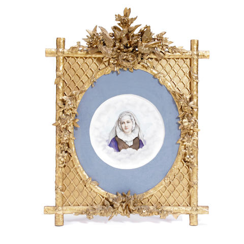 A Limoges porcelain portrait charger with elaborate giltwood frame