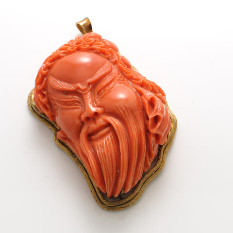A carved coral and gold pendant