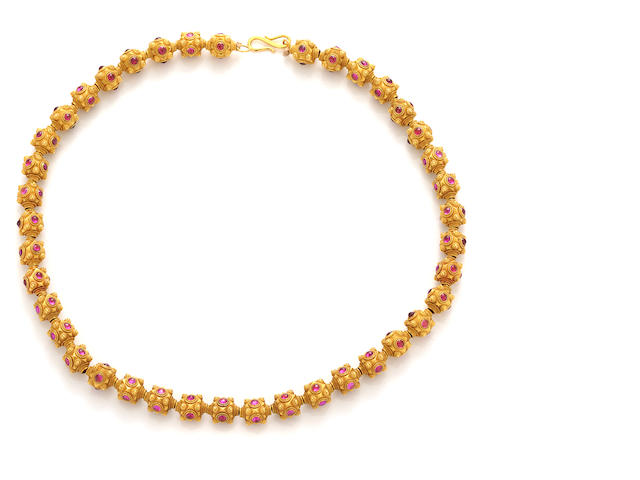 A glass-filled ruby and eighteen karat gold bead necklace