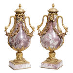 A pair of Louis XVI style gilt bronze mounted marble covered urns