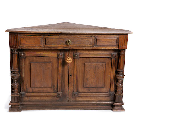 A Continental Baroque style mixed wood corner cupboard