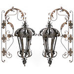 A pair of Victorian style wrought iron and tôle wall lanterns with brackets