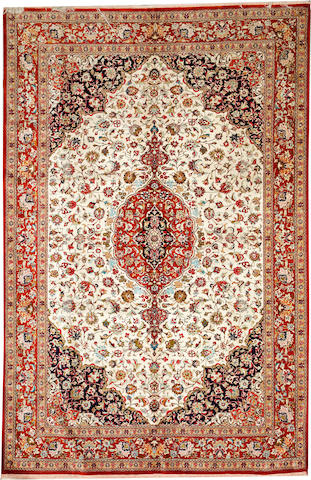 A Qum Silk rug  3rd quarter 20th century size approximately 6ft. 7in. x 10ft. 4in.