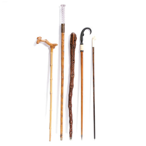 A large collection of metal, bone and glass mounted hardwood walking sticks