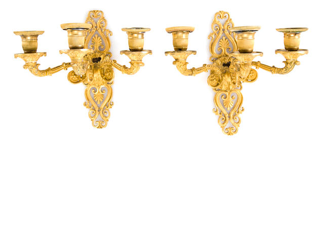 A pair of Restauration gilt bronze three-light wall sconces, 19th century, each scrolled backplate with palmettes, formerly electrified, drilled, height