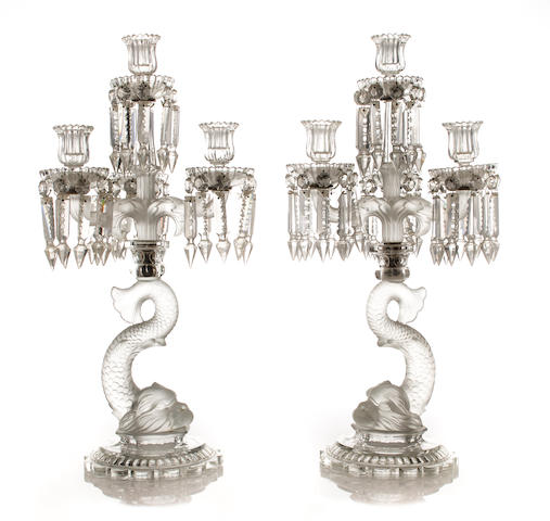 A pair of French partially frosted molded glass four-light candelabra with dolphin-form standard<BR />Baccarat, early 20th century