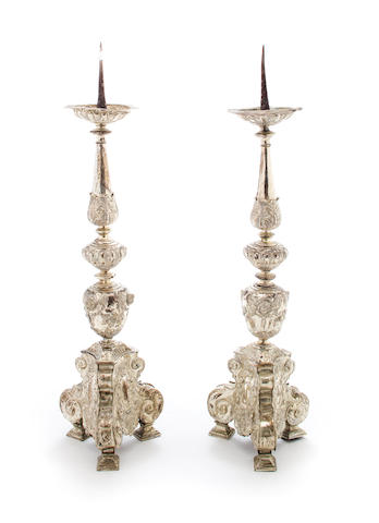 A pair of silver plated altar sticks, each of knopped form with putti heads on a scrolled tripartite base, height 25in