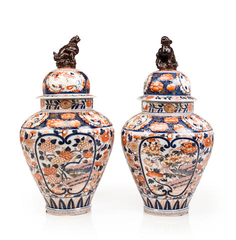 A pair of Imari-style blue and orange jars with sealed lids