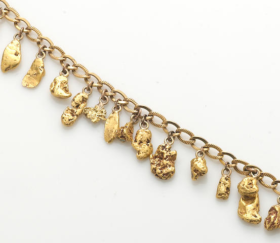 A 14k gold bracelet suspending twenty one gold nugget, 14k gold and metal charms