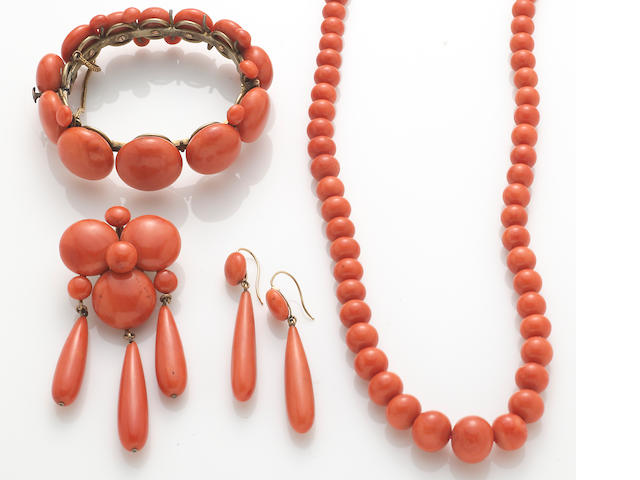 A collection of coral, gold, and metal jewelry