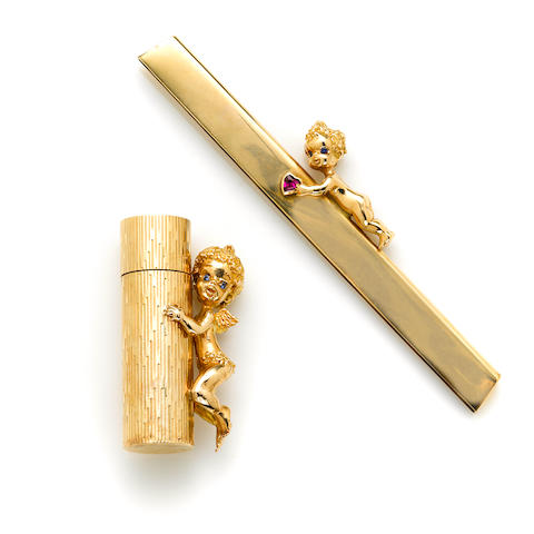 A 14 karat gold perfume bottle, Ruser Embellished with a cherub. together with A 14 karat gold comb surmount, Ruser Embellished with a cherub. (comb removed)