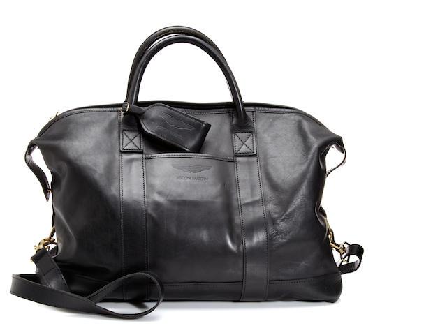 An Aston Martin black leather travel bag