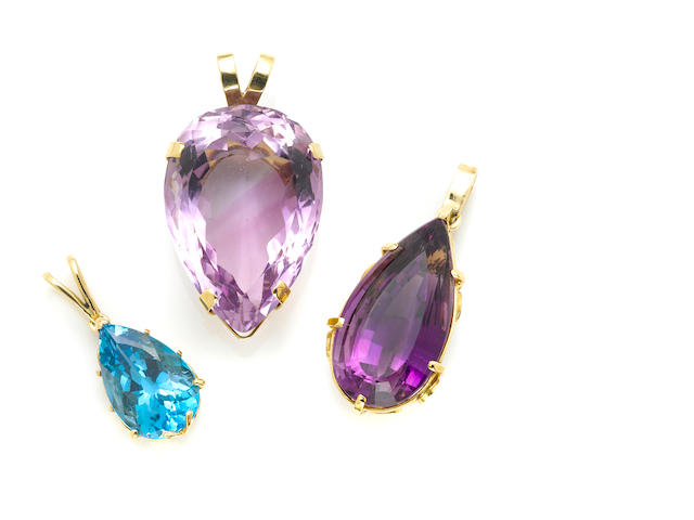 A collection of three amethyst, topaz and gold pendants