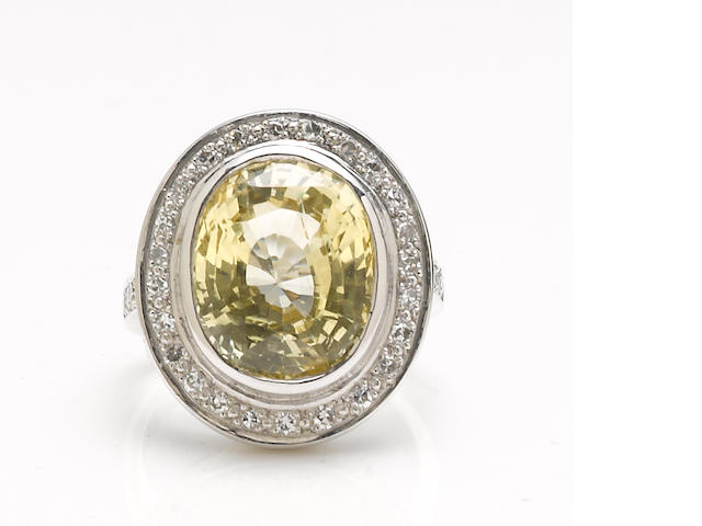 A yellow sapphire, diamond and 18k white gold ring