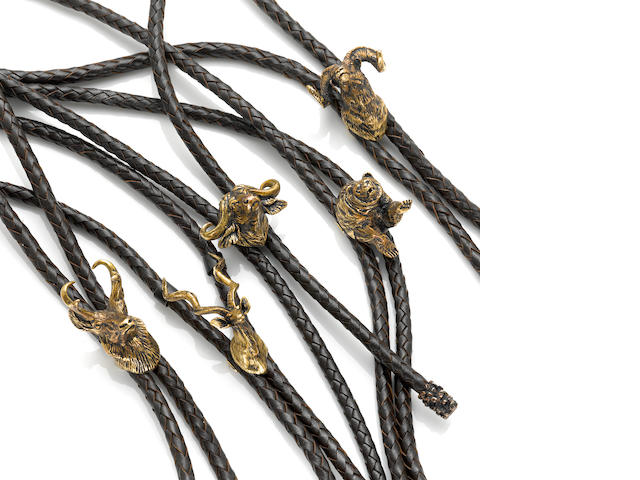 A collection of five gold and leather bolo ties